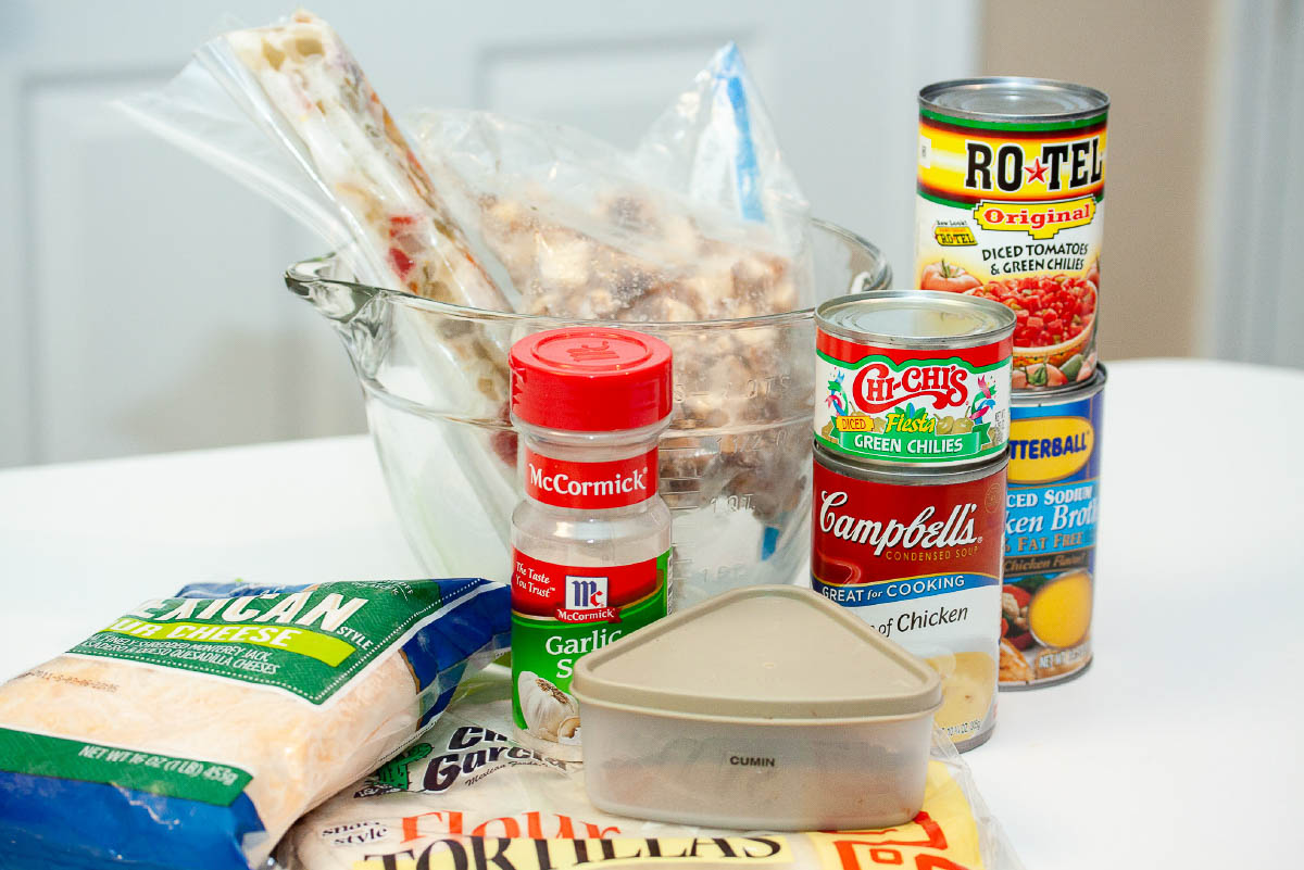 Ingredients for creamy chicken enchiladas: cooked chicken, cooked onion & bell peppers, cumin, garlic salt, green chilis, Rotel tomatoes and green chilis, chicken broth, shredded Mexican cheese, and flour tortillas