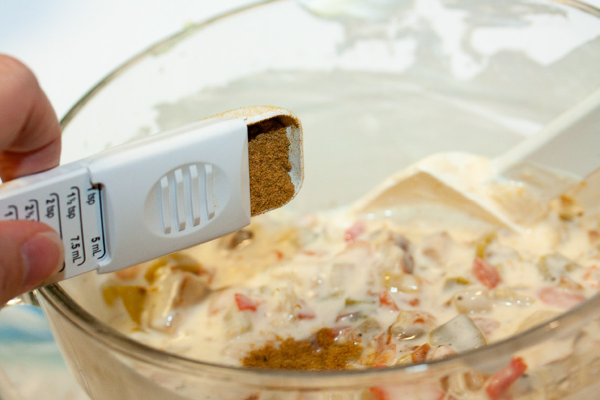 Cumin being dumped into a bowl of white cream sauce with chicken and peppers