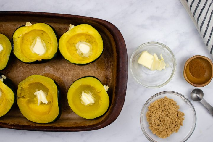 Acorn squash halved and steamed in a pan with a pat of butter inside the indentation of each half