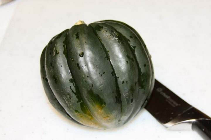Whole acorn squash on a cutting board with a knife