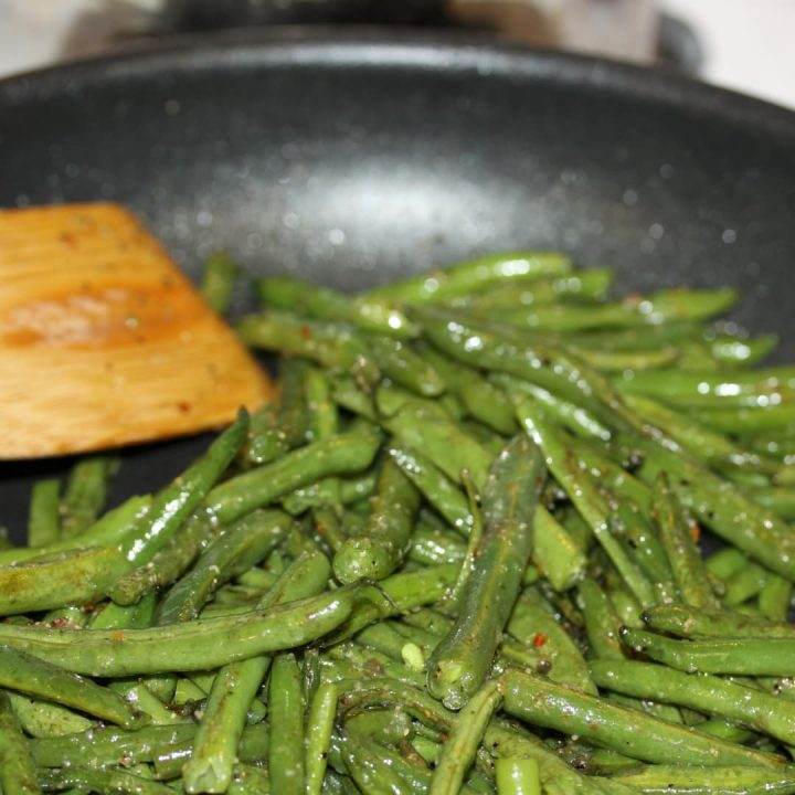 Sautéed seasoned green beans in a black frypan