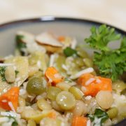 Lentils, carrots, artichokes, and almonds in a bowl topped with dressing and shredded parmesan cheese, garnished with parsley