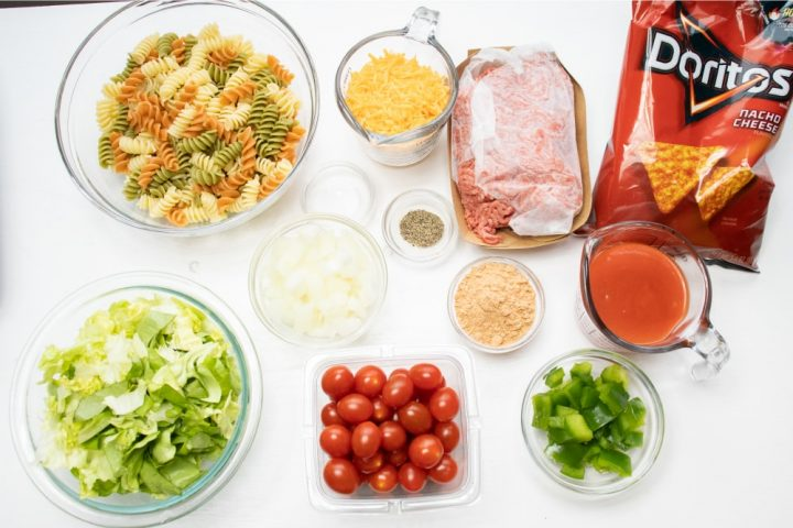 Overhead shot of ingredients cooked spiral pasta, lettuce, chopped onion, cherry tomatoes, chopped green bell pepper, taco seasoning mix, salt, pepper, shredded cheddar cheese, ground beef, and nacho cheese Doritos