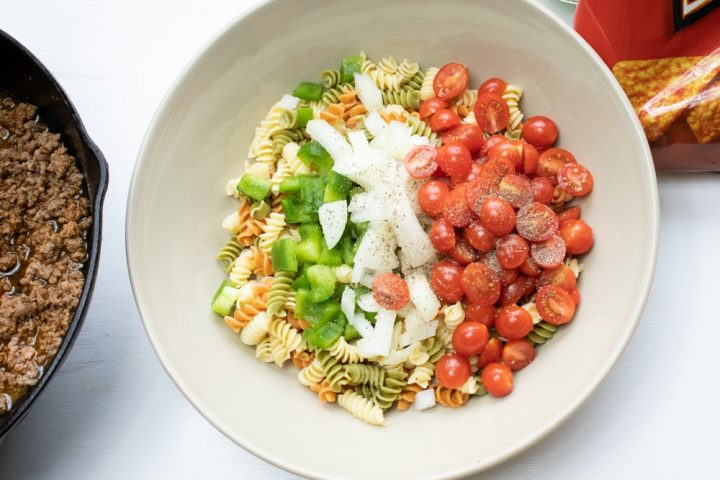 Overhead shot of cooked spiral pasta, chopped green bell pepper, chopped onion, and halved grape tomatoes