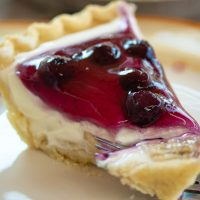 Sideview of a slice of cream pie with blueberry topping on a plate with a bit on a fork