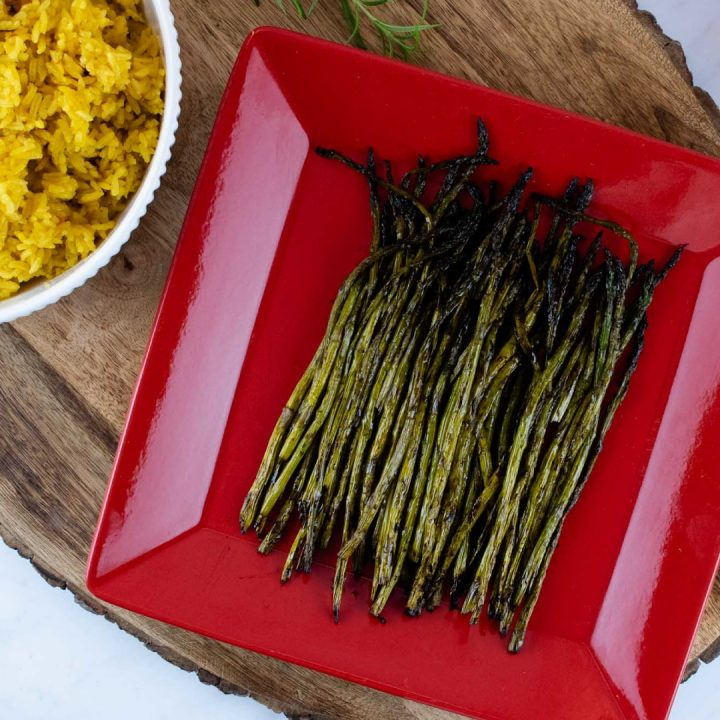 grilled asparagus on a red serving plate placed on a wood serving tray with a bowl of yellow rice and a tea towel to the side