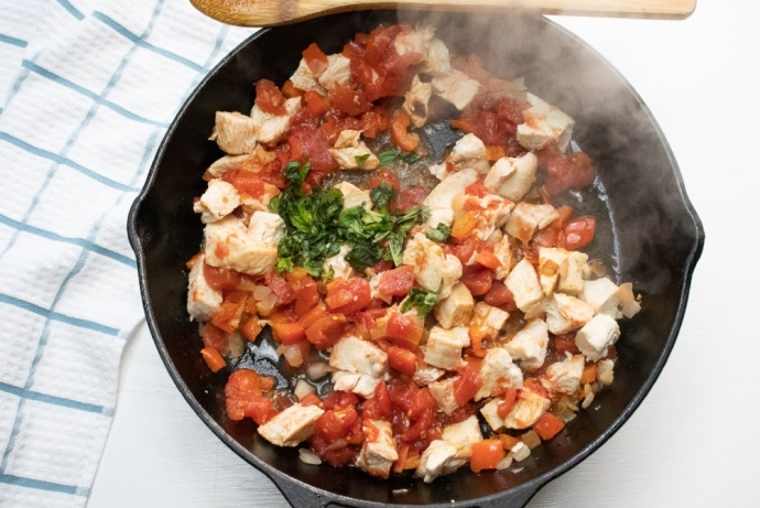 Cast iron skillet cooking chopped chicken, diced tomatoes, and fresh basil