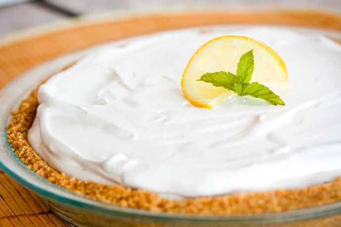 Pie with white frozen filling and graham cracker crust garnished with a twisted slice of lemon and mint with text Frozen Lemonade Pie Add Salt & Serve