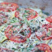 Cooked dish of layered slices of tomatoes, zucchini, yellow squash, and cheese with herbs and spices