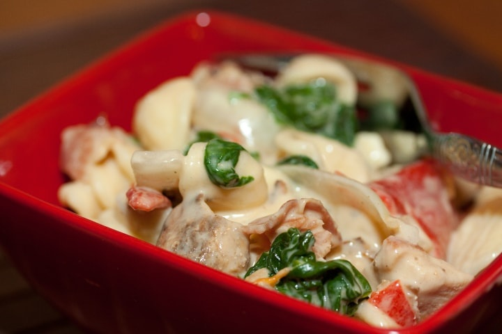 Red square bowl with orecchiette pasta, sliced onion, chopped bacon, roasted bell peppers, cooked spinach, and Alfredo sauce. There is a fork in the bowl.