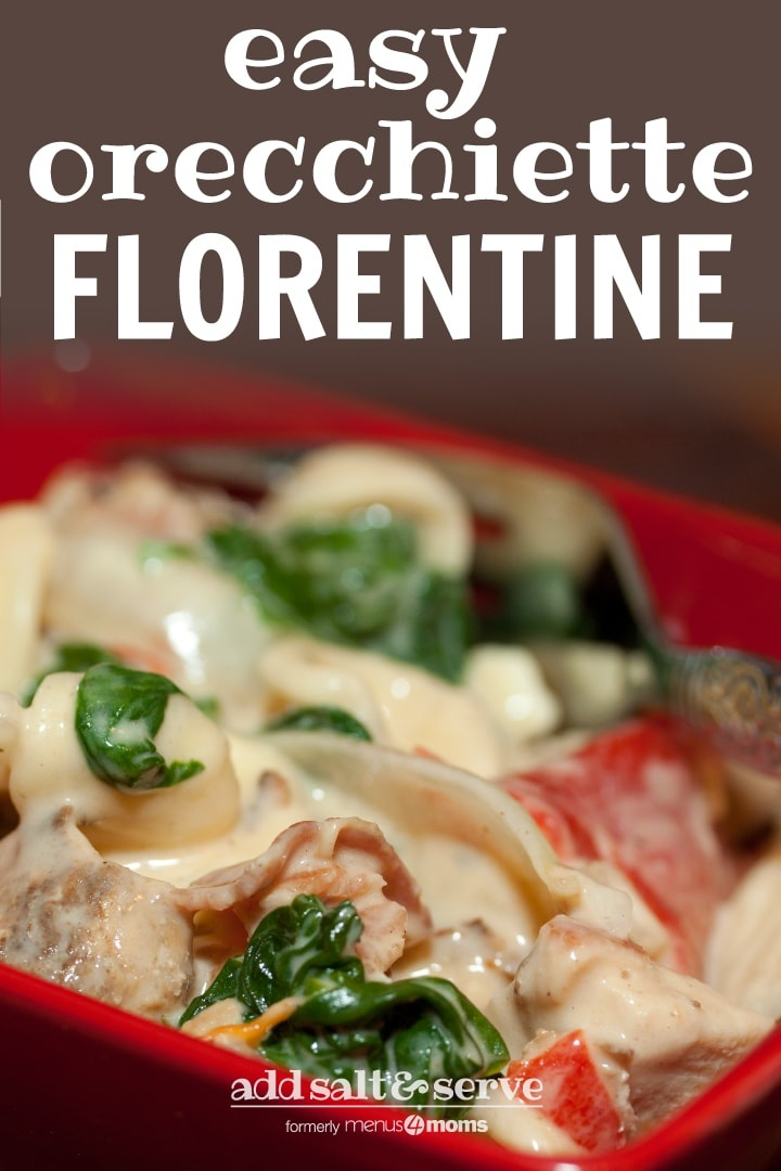 Red square bowl with orecchiette pasta, sliced onion, chopped bacon, roasted bell peppers, cooked spinach, and Alfredo sauce. There is a fork in the bowl. Text Easy Orecchiette Florentine Add Salt & Serve formerly menus4moms