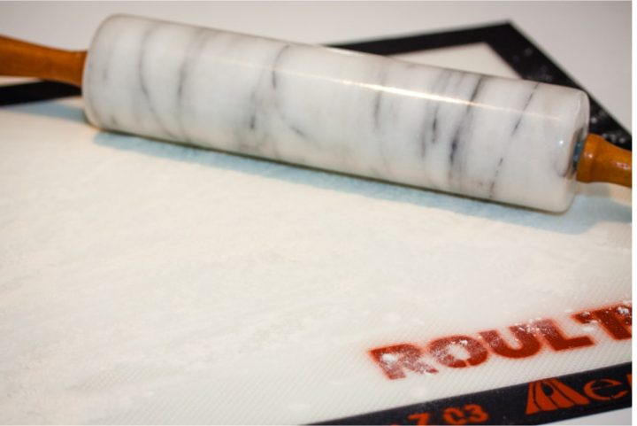 Silicone mat with flour sprinkled on it and a marble rolling pin to the side
