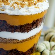 Image of layers of pumpkin filling, crushed gingersnaps, crumbled gingerbread, and whipped cream in a trifle bowl