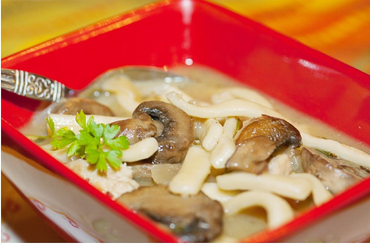 A red square soup bowl with a soup with sliced mushrooms and linguini. There is a spoon in the bowl.
