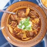 Overhead shot of albondigas soup (Mexican meatball soup) in a brown wide-rim bowl garnished with sour cream, grated cheddar cheese, and fresh cilantro