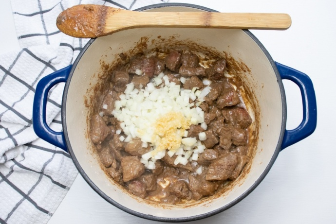 Beef stew in a pot with chopped raw onions and garlic added
