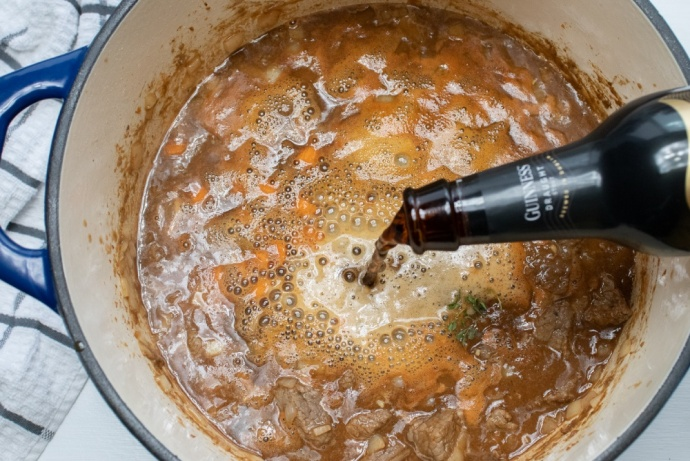Pot of Beef Stew with Guinness beer pouring in