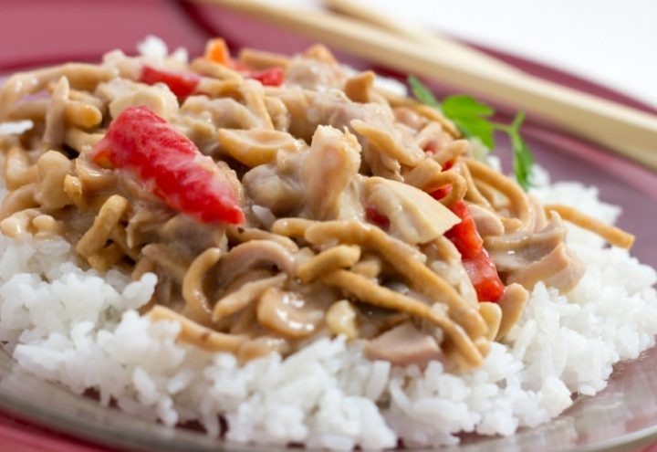 Chopped chicken with red peppers and mushrooms in a creamy sauce over white rice and garnished with chow mein noodles