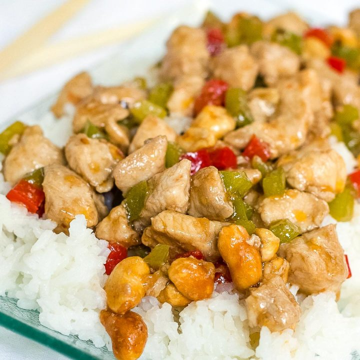 Diced chicken and diced red and green bell peppers on a bed of rice on a transparent square glass plate.