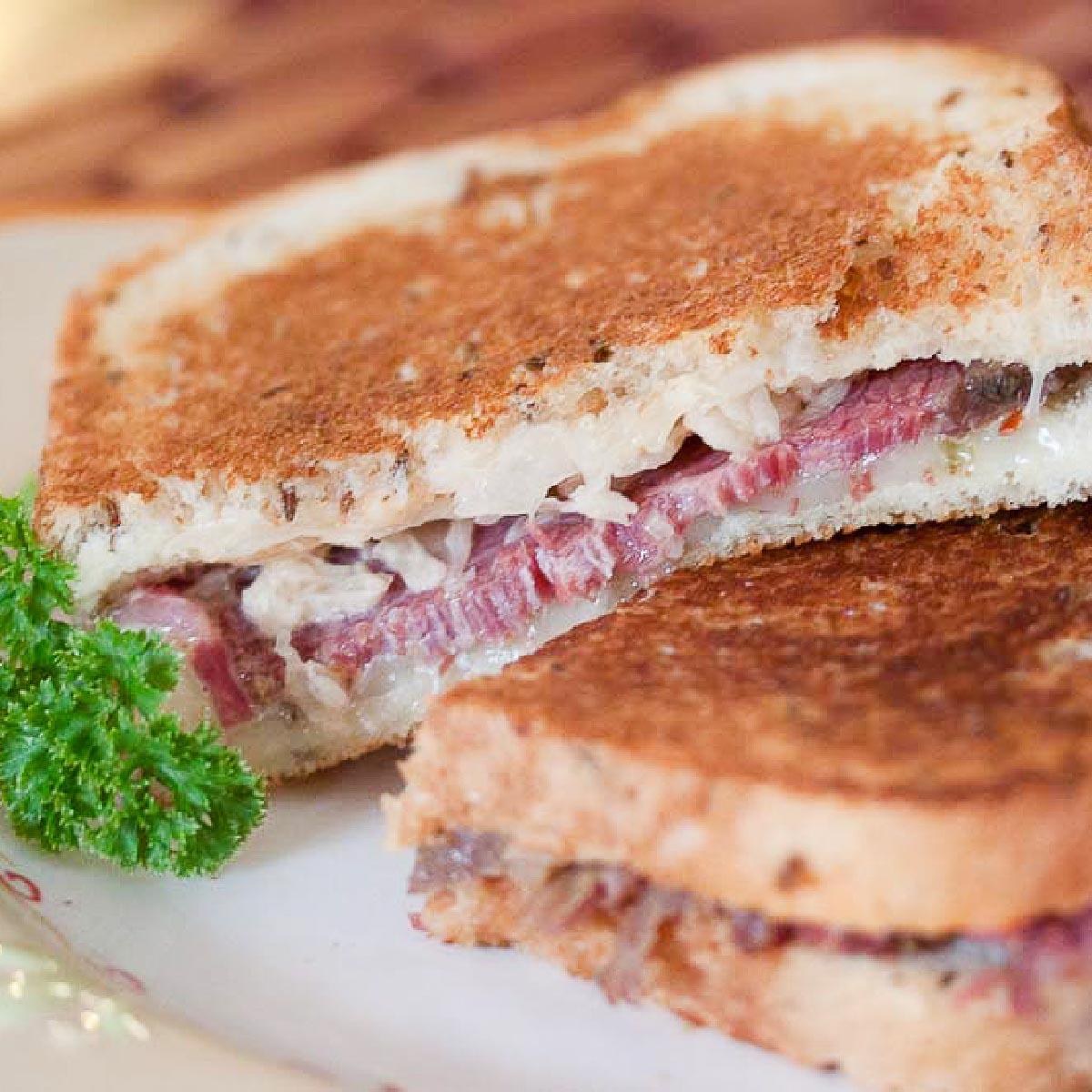 Two Reuben sandwiches on a white plate.