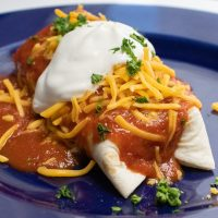 Blue plate with a burrito covered in red sauce and garnished with cheese, sour cream, and cilanto