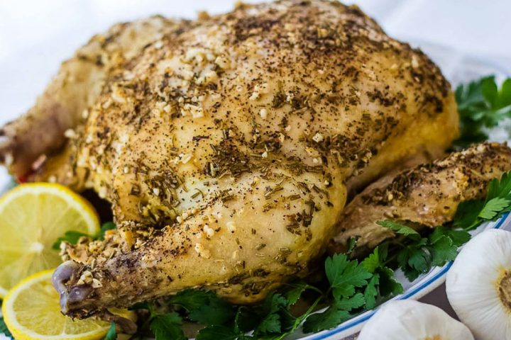 Whole roasted chicken with a dried rosemary and minced garlic rub on a white plate, garnished with lemon slices and parsley. There are two bulbs of garlic beside the plate in the bottom right corner.
