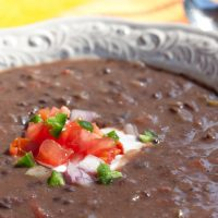 A white shallow bowl with Black Bean Soup garnished with sour cream, diced tomatoes, diced red onion, and fresh cilantro