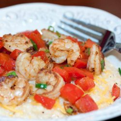 Shrimp, diced tomatoes, and shredded cheddar cheese on grits, on a white plate with a fork.