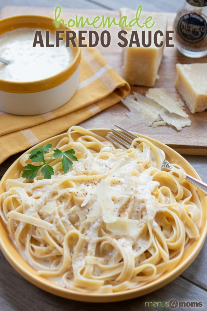 Yellow plate with fettuccine and Alfredo sauce with pot of Alfredo sauce, hunk of Parmesan cheese, and nutmeg grinder in background; text Homemade Alfredo Sauce Add Salt & Serve