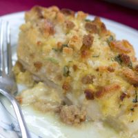 Chicken covered in cream sauce with browned stuffing on top served on a white plate with a fork and text Baked Swiss Chicken
