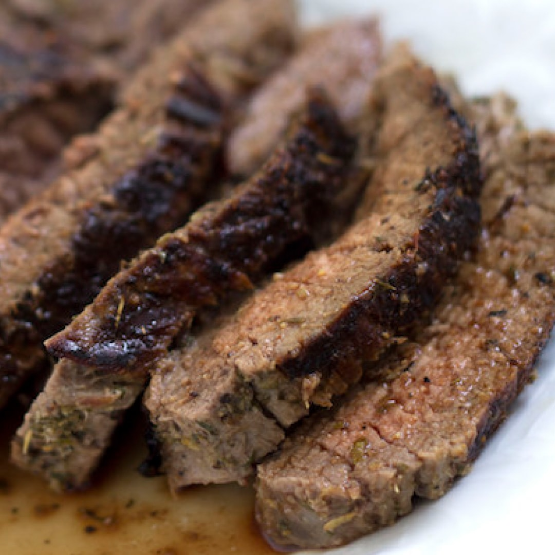 Seaasoned and grilled flank steak sliced and plated with juices