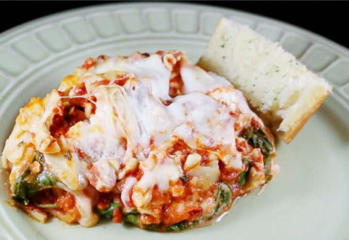 Lasagna with spinach, tomato sauce, and melted mozzarella cheese on a plate with a slice of italian bread