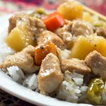 Chunks of cooked chicken, pinapple, carrots, and peppers served over white rice