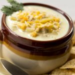 Brown crock with chicken corn chowder garnished with cilantro and surrounded by tortilla chips