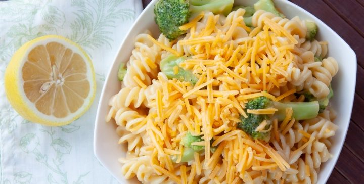 Cheddary Spirals with Broccoli garnished with cheese in a white bowl beside a lemon half on a green and white towel