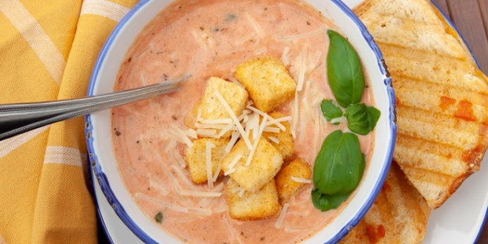 Creamy Tomato Basil Soup in a white bowl with blue trim garnished with croutons, Parmesan cheese, and fresh basil and served with a grilled cheese sandwich