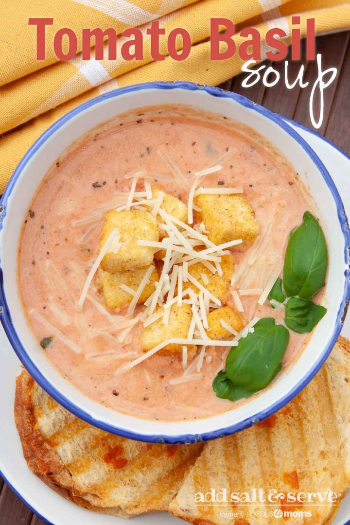 Creamy Tomato Basil Soup in a white and blue bowl, topped with croutons and shredded parmesan cheese. The bowl is on a plate with two slices of garlic bread. Text Tomato Basil Soup Add Salt & Serve formerly Menus4Moms