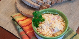 Homemade Pimento Cheese in a green and white crock beside a loaf of bread and a mulit-colored towel