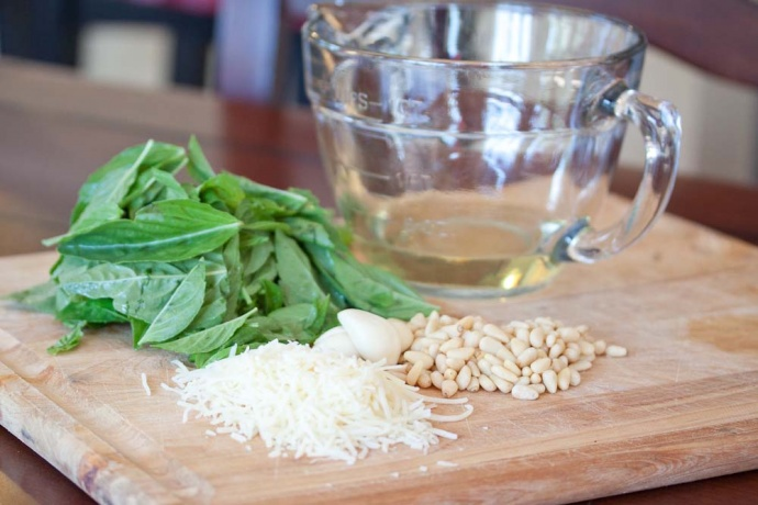 image of a cutting board with a pile of basil leaves, cloves of garlic, a pile of pine nuts, a pile of shredded Parmesan cheese, and a measuring cup with oil