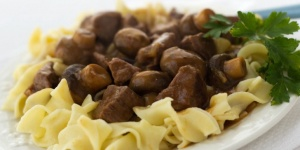 Slow Cooker Beef and Mushrooms over egg noodles in a white bowl with parsley garnish