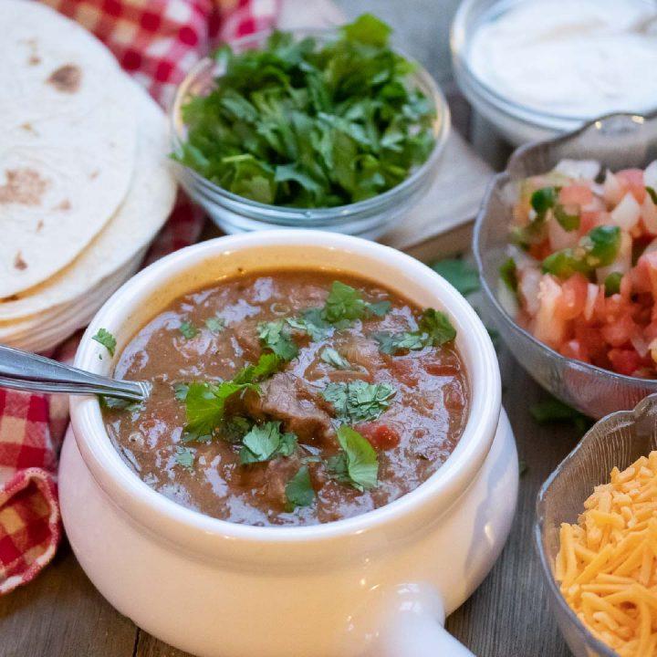 Carne Guisada (Mexican Beef Stew) in a white crock with cheese, tortillas, fresh cilantro, sour cream, and pico de gallo