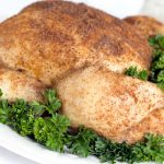 Whole cooked chicken covered with spices, on a white plate garnished with a lot of parsley.