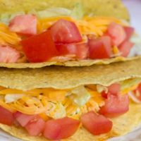 Tacos with shredded lettuce, grated cheese, and chopped tomatoes