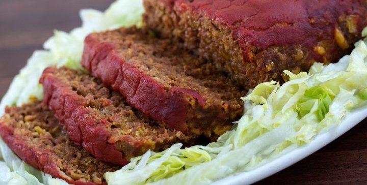 Sliced Taco Meatloaf on a white platter with lettuce garnish