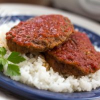 Baked Swiss Hamburgers over rice garnished with parsley