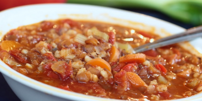 Soup with barley, lentils, carrots, tomatoes, and broth in a white bowl