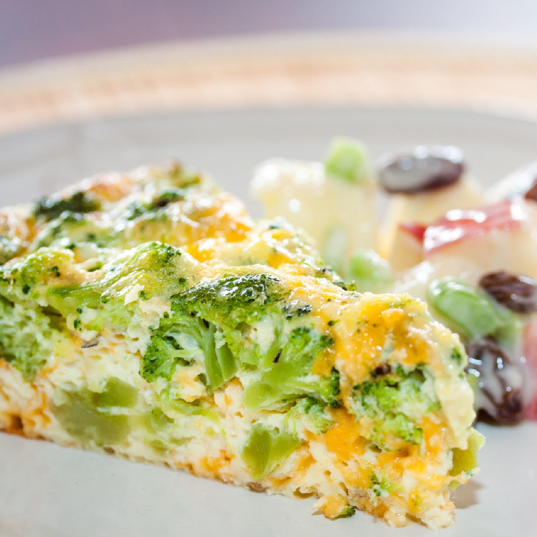 Slice of broccoli and cheese quiche on a plate with apple and raisin salad on a white plate.