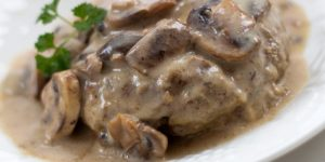 Cooked beef patty in mushroom sauce on a white plate