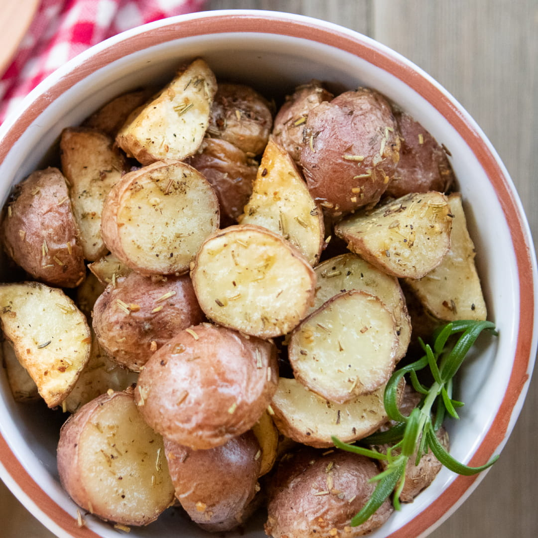 Bowl of chopped roasted and seasoned new potatoes with a red checked towel and a wooden spoon to the side and text Roasted Red Potatoes