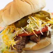 White bun piled with grilled flap meat, lettuce, tomato, cheese, and jalapeno slices